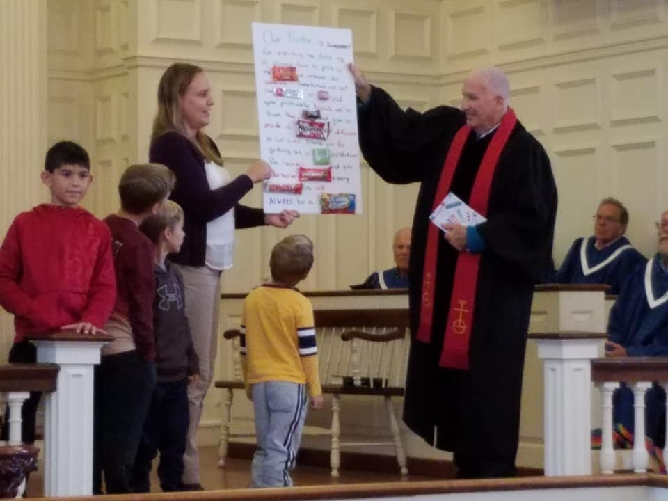 children presenting a poster board to the church pastor