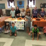 kids in the youth group gathered around a table of baked goods